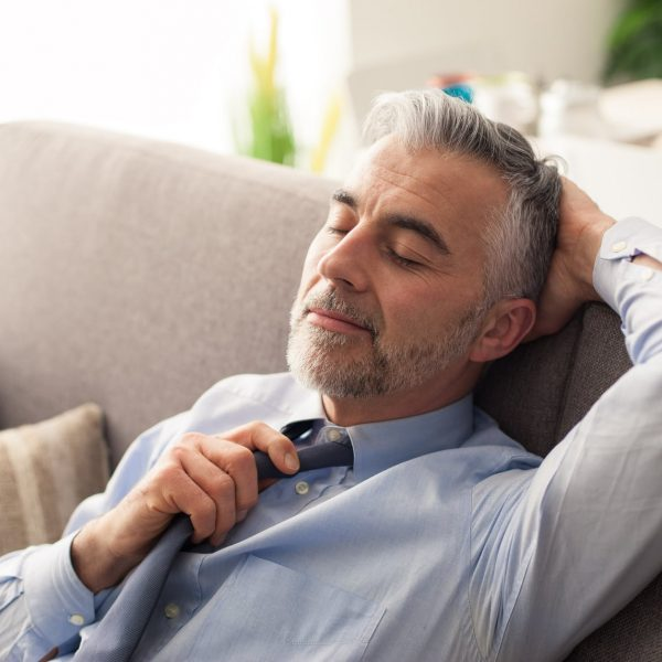 Happy businessman relaxing at home on the couch, he is loosening his tie